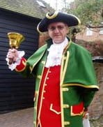 Town crier in green cloak, red waistcoat and tricorn hat, ringing bell.