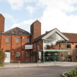 Outside of Farnham Maltings. Red brick building. Glass fronted entrance.