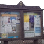 Wooden noticeboard. Posters