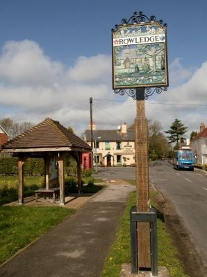 Bus shelter left, Rowledge village sign, pub in background
