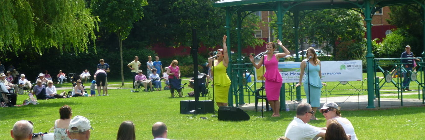 People watching three female singers at Music in the Meadow. © Farnham Town Council