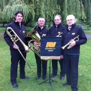 Four male members of brass band. Music stand. Brass instruments.