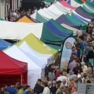 Aerial view of people and colourful market stalls at Food Festival held in street.