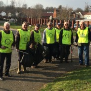 Seven men in high viz vest collecting litter.