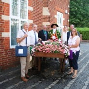 People standing next to hop cart filled with flowers