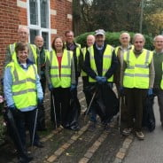 Councillors in high visibility jackets holding litter pickers and sacks of rubbish.