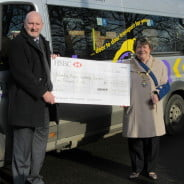 Man and Mayor stand to the side of a community bus holding large cheque