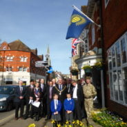 A group of people including soldiers, the Mayor and two children stand beneath Commonwealth flag.