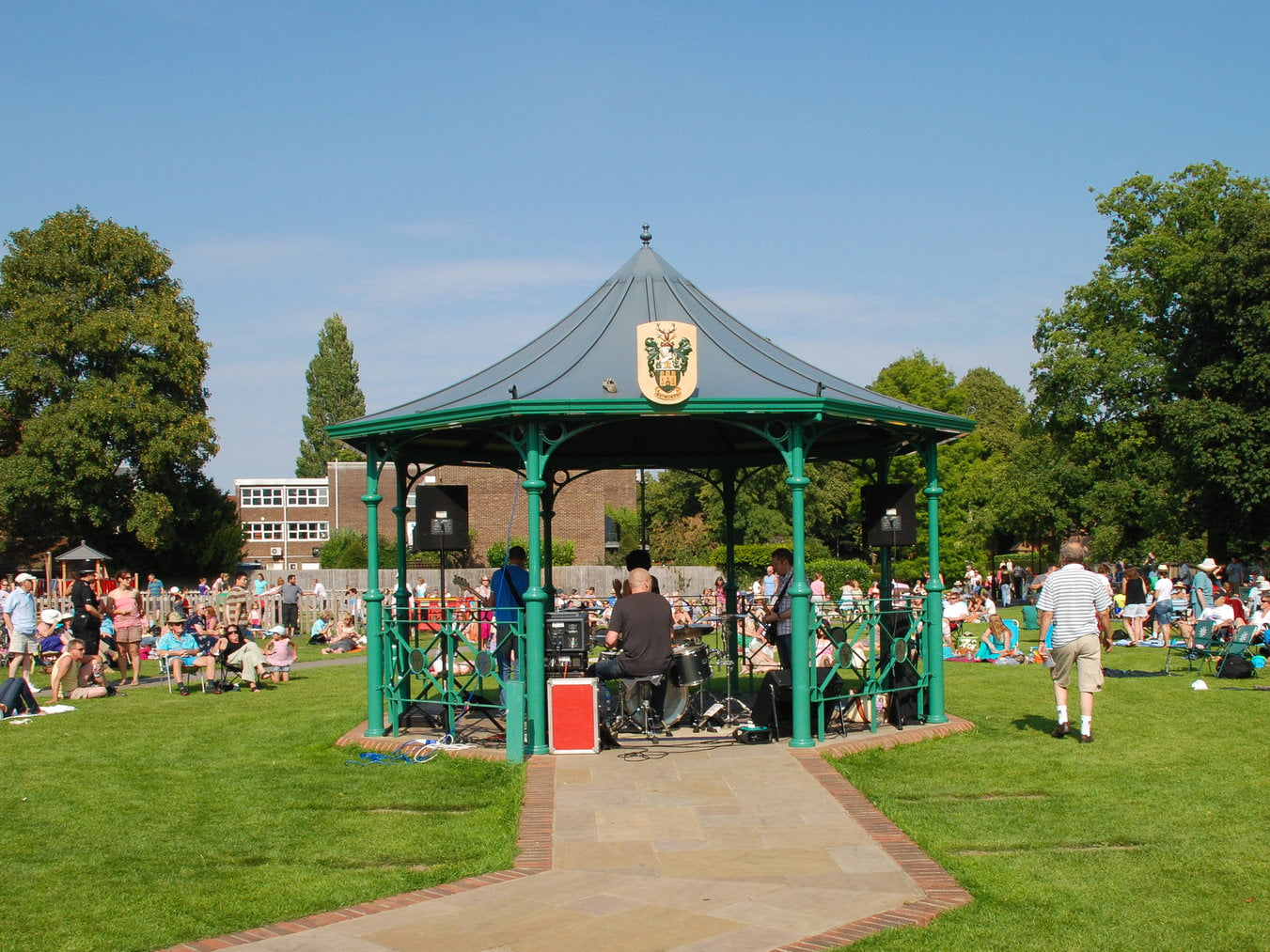 People watching a band play in a bandstand in a park.