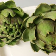 Two fresh green artichokes on a white plate