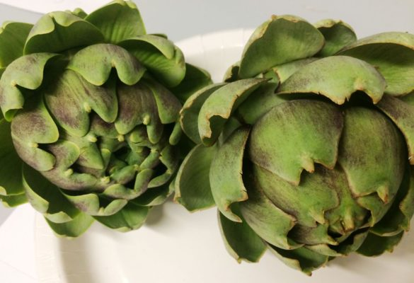 Two fresh green artichokes on a white plate