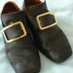 Black leather shoes with gold coloured buckle.