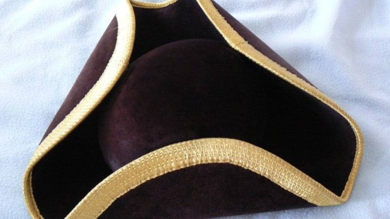 Black tricorn hat with gold edging.