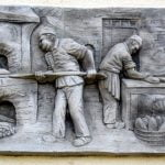 Plaque showing bakers putting bread in oven