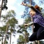 Girl leaping in the air. Tall trees in background