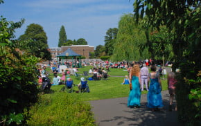 People sitting in Gostrey Meadow. Music, bandstand, summer's day.
