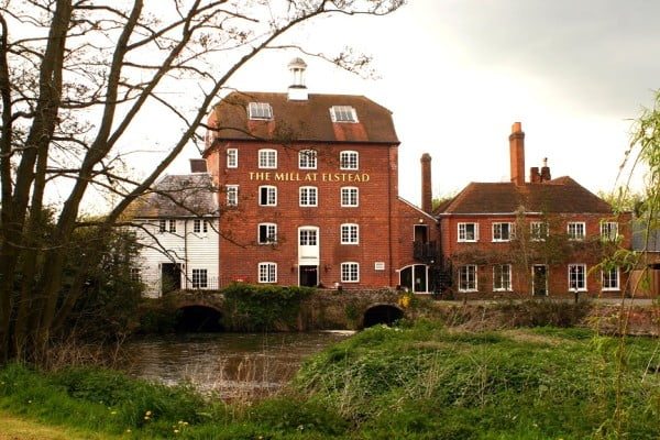 Large red brick building, river and grass surrounding.
