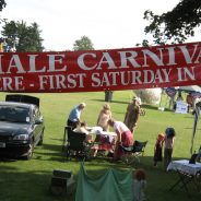 Banner advertising Hale Carnival. People setting up stalls for fete.