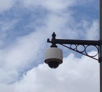 CCTV camera on decorative bracket. Blue sky and white clouds. © Farnham Town Council