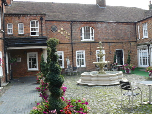 courtyard with brick building and stone fountain in the center, decorative plants around the edge.
