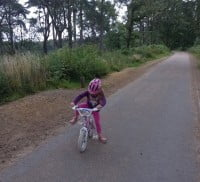 child on bike, woodland surrounding pathway.