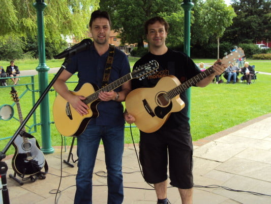 Two males with acoustic guitars standing under bandstand.
