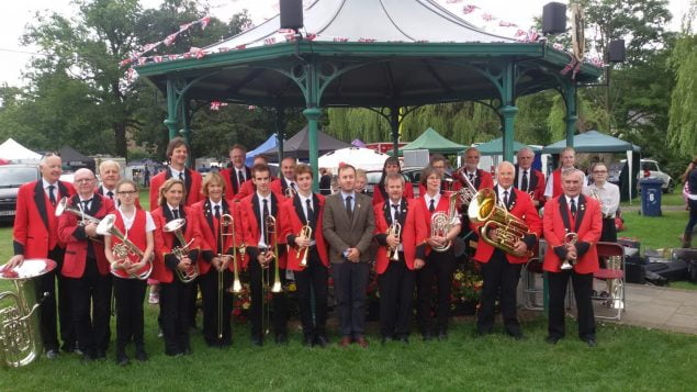 Group of male and female brass band members standing in front of band stand.