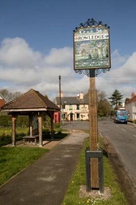 Bus shelter left, Rowledge village sign, pub in background