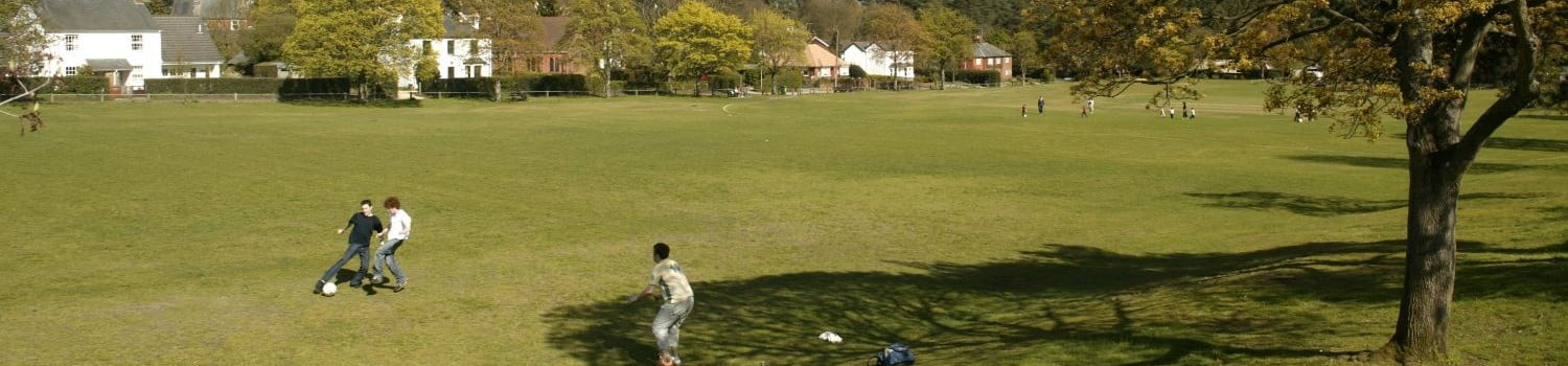 Three men playing football on village green. Large open green space with houses in foreground.
