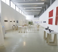 Inside an art gallery. Table in middle of room and art on the wall
