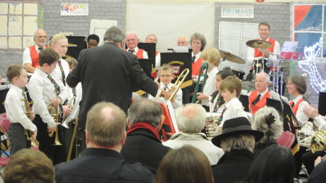 group of children playing instruments, smartly dressed. Audience in foreground.