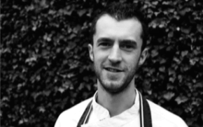 Black and white head and shoulders photo of man wearing chef's whites. © The Wheatsheaf Pub & Grill