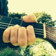 Hand, guitar neck, sky, trees.