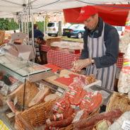 Stall with various meats and male stallholder