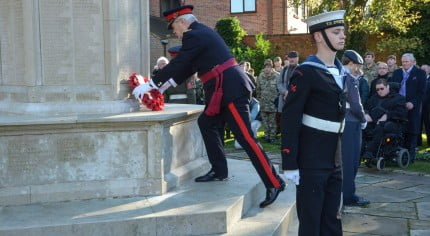 Male laying wreath on war memorial, group to the right watching, male in uniform in foreground