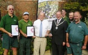 Seven men including Mayor, holding certificates and trophy for Farnham in Bloom.