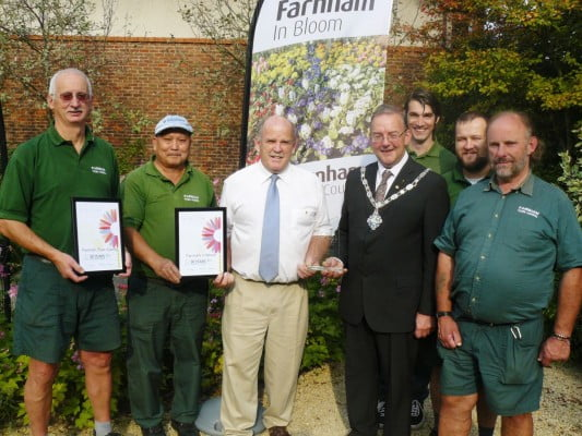 Seven men including Mayor, holding certificates and trophy for Farnham in Bloom.