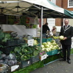 Mayor holds a cauliflower in front of vegetable stall at Food Festival.