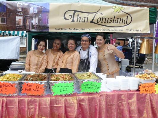 Five people behind stall serving food.