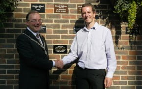 Mayor and man shake hands in front of brick wall after unveiling a commemorative plaque.