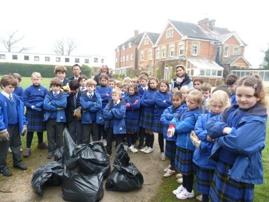 Group school children, blue uniform, litter pick, sacks of rubbish, school