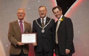 Three men including Mayor holding certificate.