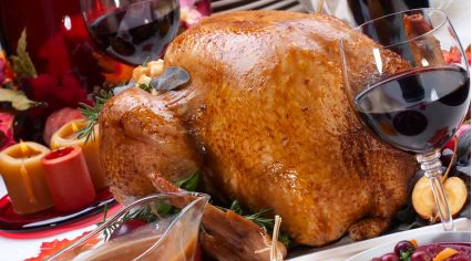 cooked turkey with gravy and wine on the table.