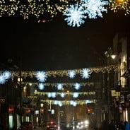 Across street Christmas lights.White stars and gold lights. Busy street. Nighttime.