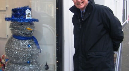 Snowman made from tinsel with blue top hat. shop window. man looking through window at snowman