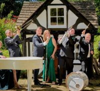 Group of people playing musical instruments in front of a pretty timber cottage