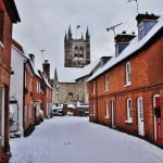 Snow, houses on left and right. Church tower in background.