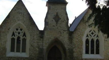 Outside stone chapel, bell turret, arched windows and door.