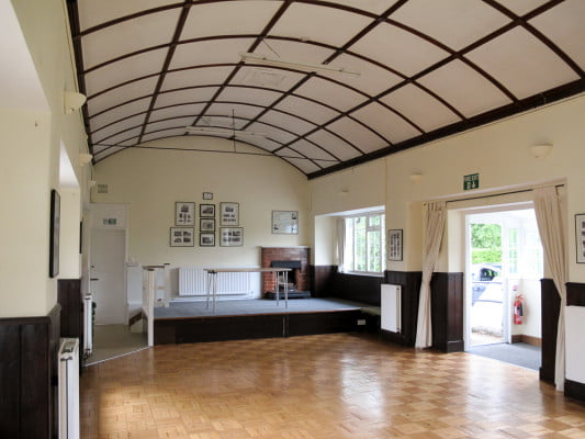 interior of village hall, domed roof, small stage with a table.