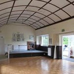 Inside view of village hall. White domed ceiling, wooden floor and large windows on right hand side